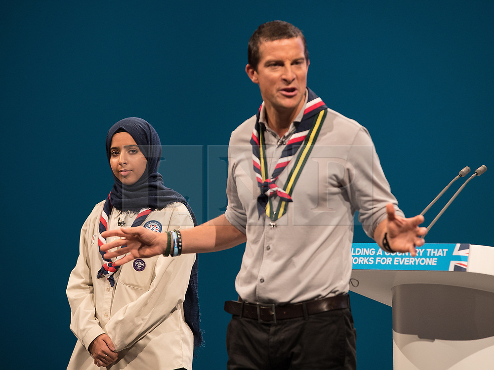 © Licensed to London News Pictures . 03/10/2017 . Manchester , UK . FERDOUS AL-AUDHALI (22 from Solihull) and Chief Scout BEAR GRYLLS on stage ahead of the Home Secretary , during day three of the Conservative Party Conference at the Manchester Central Convention Centre . Photo credit : Joel Goodman/LNP