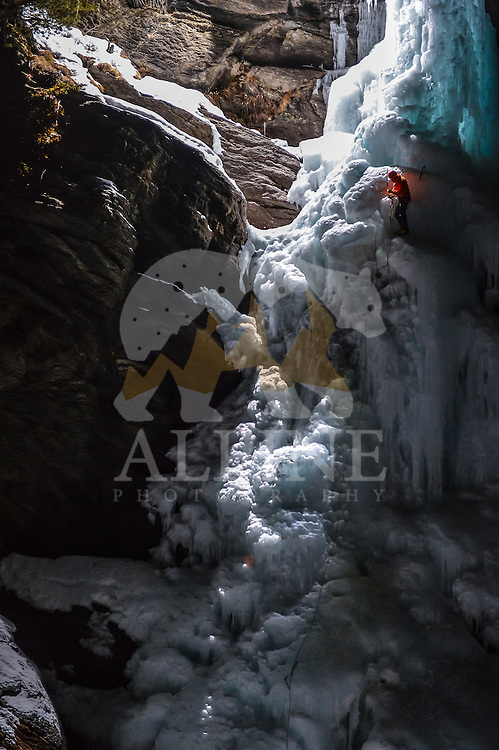 Jeff Mercier, a professional alpine climber resting on hanging belay during a night ascent of Cascate di Lillaz icefall.