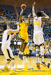 Dec 5, 2015; Morgantown, WV, USA; Kennesaw State Owls guard Kyle Clarke (11) shoots a layup over West Virginia Mountaineers forward Brandon Watkins (20) during the first half at WVU Coliseum. Mandatory Credit: Ben Queen-USA TODAY Sports