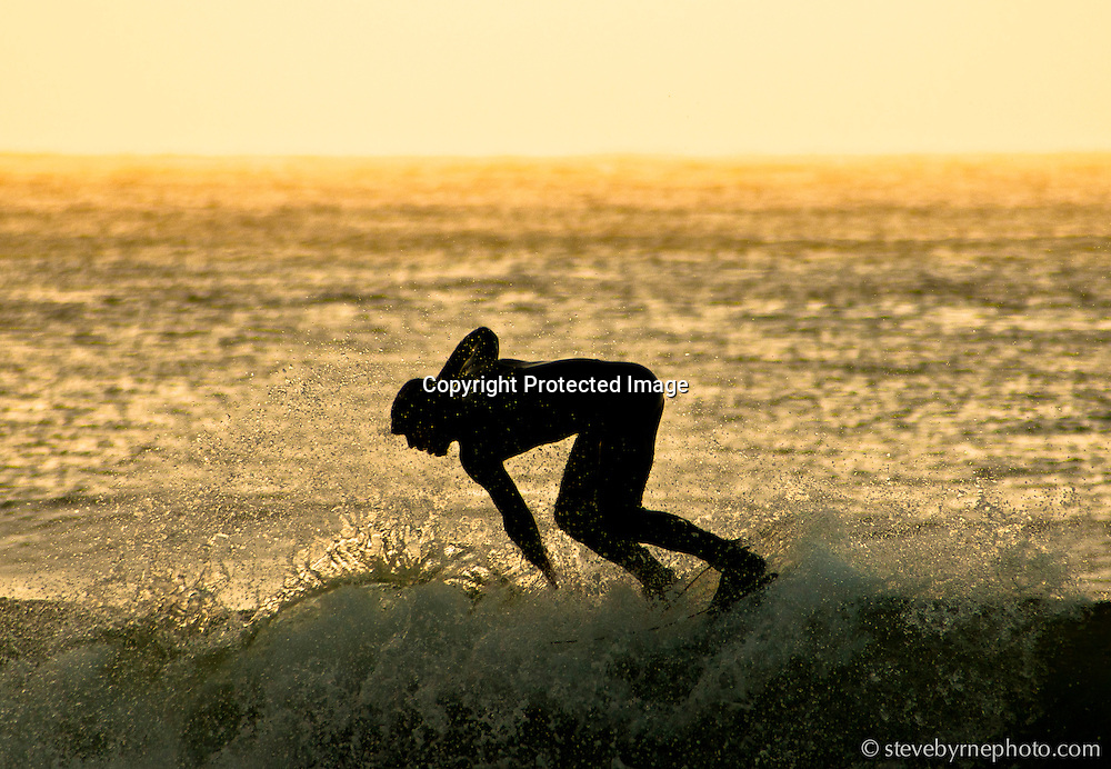 Under the glow of a late December evening, a surfer in San Francisco cuts back and rides the lip of a closing wave.