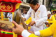 14 OCTOBER 2012 - BANGKOK, THAILAND:  Men play gongs and drums during a procession on the first day of the Vegetarian Festival in Bangkok's Chinatown. The Vegetarian Festival is celebrated throughout Thailand. It is the Thai version of the The Nine Emperor Gods Festival, a nine-day Taoist celebration beginning on the eve of 9th lunar month of the Chinese calendar. During a period of nine days, those who are participating in the festival dress all in white and abstain from eating meat, poultry, seafood, and dairy products. Vendors and proprietors of restaurants indicate that vegetarian food is for sale by putting a yellow flag out with Thai characters for meatless written on it in red.     PHOTO BY JACK KURTZ
