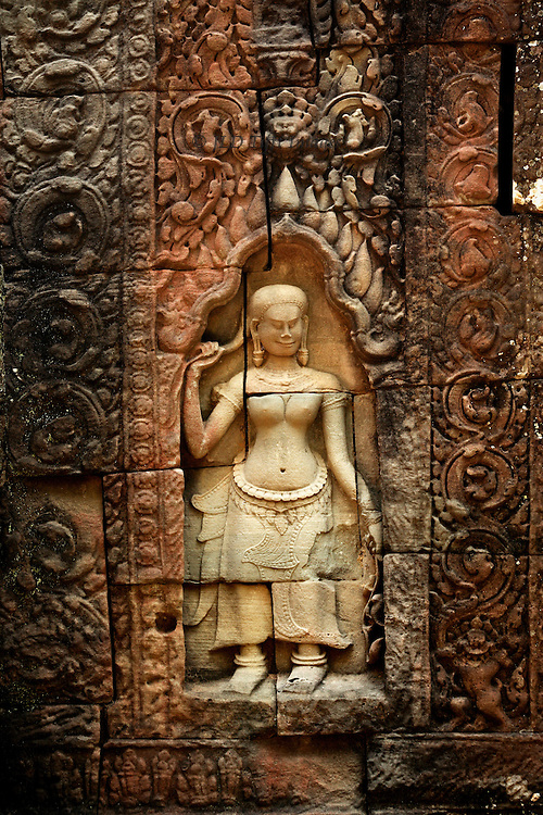 Angkor, Ta Som : detail of one Apsara dancer figure in a niche, surrounded by scrolled foliage ornament.