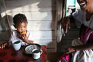 "Albertine Sampy, 41, left, laughs while feeding her 2 year old granddaughter Elshyrah, at their home in Brickaville, Madagascar. ""We had to fight against death,"" says Albertine  of Cyclone Giovanna. The brutal winds that tore off the roof of her house and destroyed 60 lychee trees that produced 1.5 tons of fruit each year. Coupled with the loss of her rice fields Albertine lost 80 percent of her income and calculates it will take at least 5 years for her trees to begin producing again and for life to resume to normal. Sara A. Fajardo/Catholic Relief Services"