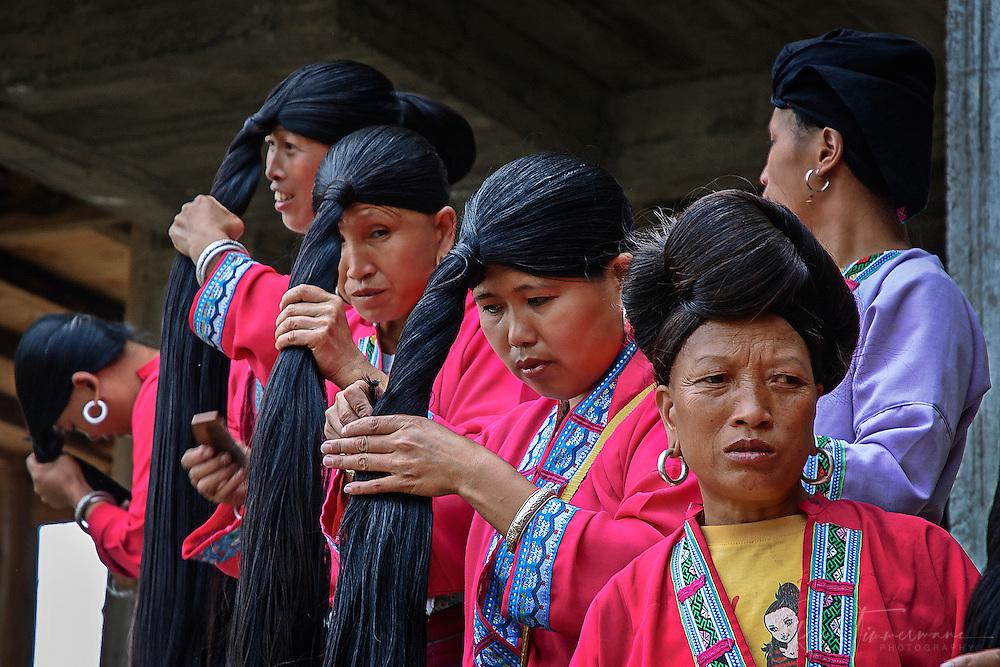 Tribal Zhuang women are brushing their long hair.