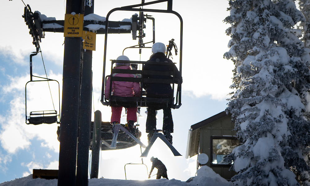 An adult and child top the Panorama Lift against an afternoon sun at Monarch Mountain.