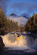 The late American expeditionary kayaker Lars Holbeck runs a waterfall on Davis Creek as the evening sun breaks through parting mist on the Seward Penninsula, Alaska.