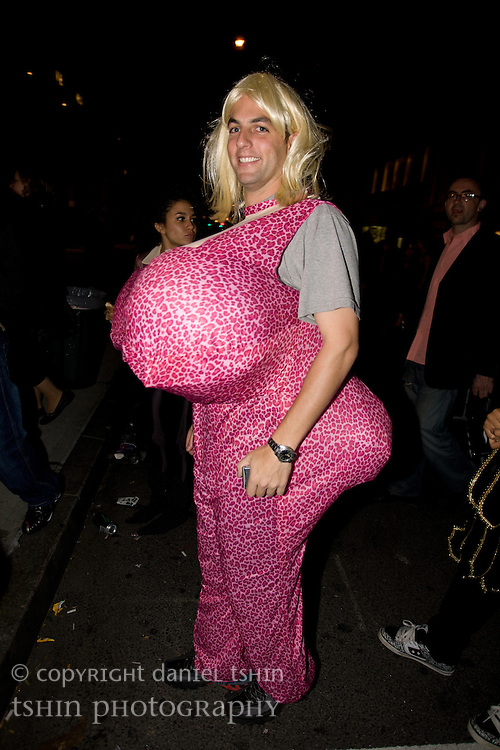 A man costumed with a blond wig, large breasts and large bottom