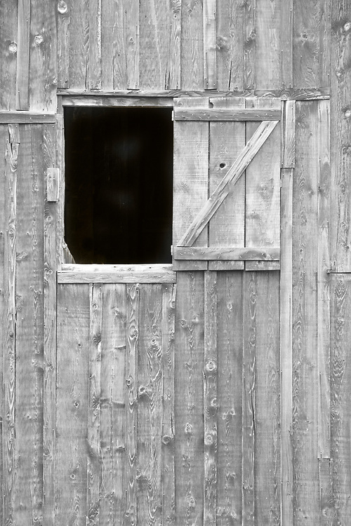 There is a mystery to what is beyond this window in the darkness of the old barn.