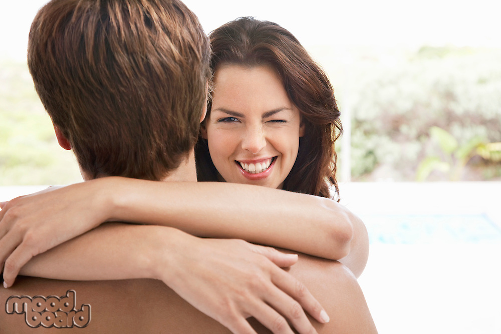Woman winking over man's shoulder head and shoulders
