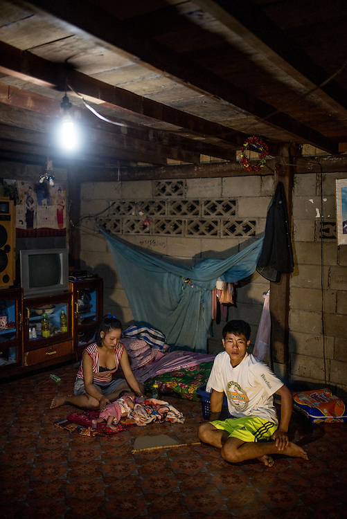 Khan Ti and his wide Mi Chanh watch over their 2 month old baby under the light of an LED bulb powered by a portable water turbine. The village of Khoc Kham is not connected to the main electrical grid and many residents operate their own turbines to power lights and sometimes small appliances.