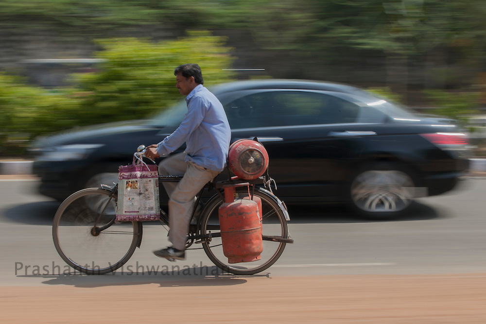 A cyclists carries Liquid Petroleum Gas cylinders on his bicycle in New Delhi, 15 March 2012. Photographer:Prashanth Vishwanathan