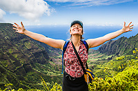 A woman on the Pihea Trail in Koke'e State Park overlooking the Kalalau Valley on the Na Pali Coast, Kauai, Hawaii, USA.