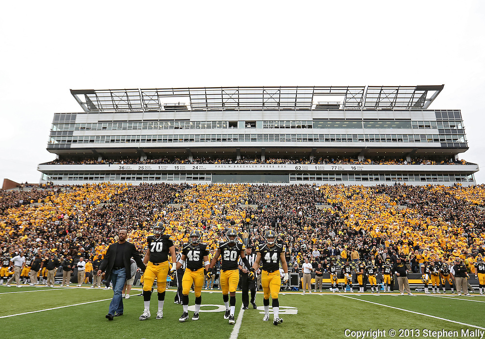 October 6 2013: Former Iowa Hawkeyes player and current Houston Astros manager Bo Porter, Iowa Hawkeyes offensive linesman Brett Van Sloten (70), Iowa Hawkeyes running back Mark Weisman (45), Iowa Hawkeyes linebacker Christian Kirksey (20), and Iowa Hawkeyes linebacker James Morris (44) walk to the center of the field for the coin toss before the start of the NCAA football game between the Michigan State Spartans and the Iowa Hawkeyes at Kinnick Stadium in Iowa City, Iowa on October 6, 2013. Michigan State defeated Iowa 26-14.