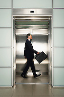 Businessman in Elevator with briefcase side view
