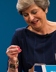 © Licensed to London News Pictures. 04/10/2017. Manchester, UK. British prime minister THERESA MAY puts a lozenge in her mouth to help unblock her throat, while delivering her leaders speech on the final day of the Conservative Party Conference. The four day event is expected to focus heavily on Brexit, with the British prime minister hoping to dampen rumours of a leadership challenge. Photo credit: Ben Cawthra/LNP