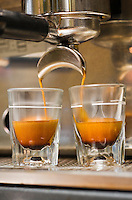 Close-up of espresso machine and shot glasses during a pour.