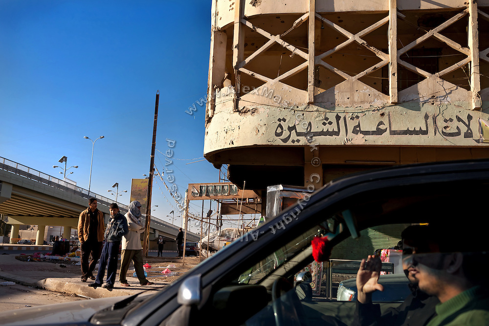 Men are waiting for daily-wage jobs, while standing at a corner next to a building still showing signs of the US-led 2004 battles on the streets of Fallujah, Iraq.