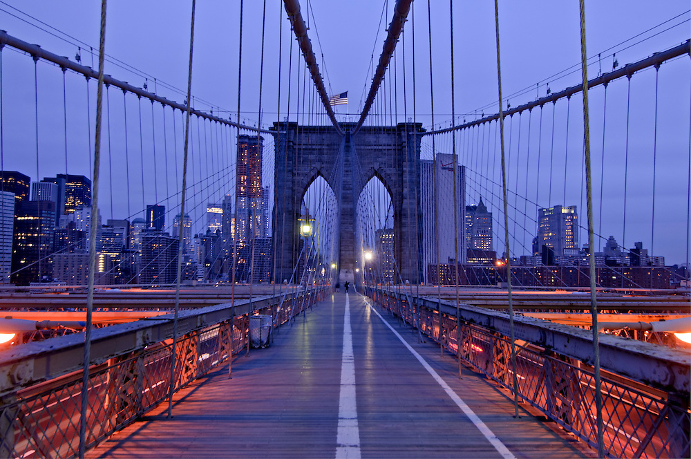 Brooklyn Bridge; New York City, NY, designed by John Augustus Roebling, on bridge looking at Manhattan, Dusk