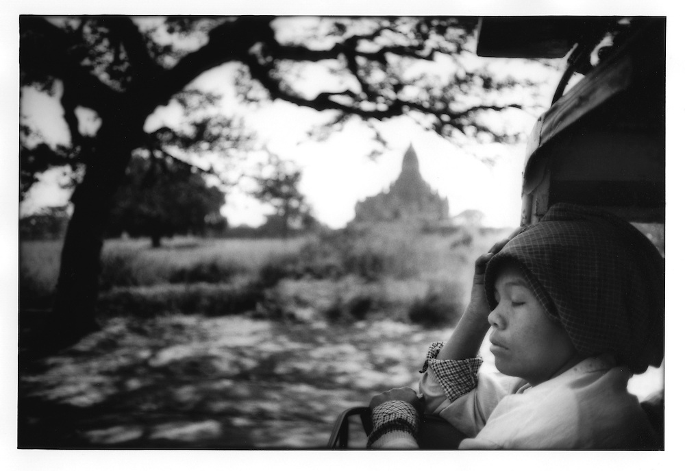 Young Burmese woman relaxes on the back of a pick up truck as it progresses through the Bagan temple complex, Burma (Myanmar).