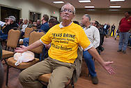 A camp owner wears a T-shirt with a protest message directed at Texas Brine at a meeting held by the company asking residents to grant them access to their land to do seismic testing. .When the Bayou Corne sinkhole opened up on August 3, 2012 a mandatory evacuation was called and many of the towns residents left. Texas Brine drilled too close too the edge of a salt mine causing it to collapse and cause an industrial disaster.
