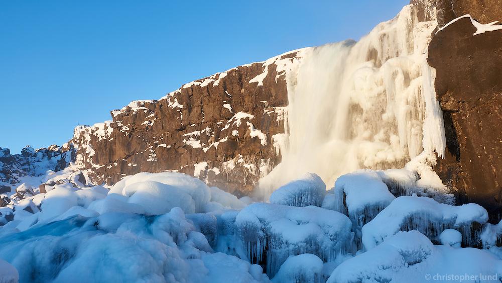 Öxaráfoss waterfall at sunrise in winter. Þingvellir National Park, South Iceland.