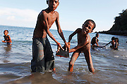 Two children argue over the ownership of the tip of a fin from a pilot whale. The Indonesian village of Lamalera has hunted whales, sharks and dolphins for the last 500 years. Their method is to leap from a small wooden boat with a long harpoon made of bamboo and spear the animal. Once brought to shore the animal is divided in to parts and distributed to the community, partly for consumption and partly for exchanging with other inland communities for corn and rice..On the 21 May 2009 at the World Oceans Conference, the Indonesian government officially declared 3.5 million hectares of critical marine habitat in the Savu Sea for conservation. Though government representatives have assured that traditional whaling -- which has been supporting the surrounding communities' means of living -- will not be banned in the area immediately outside the zone, concerns still remain. Lamalera is one of the last remaining Indonesian whaling communities and is categorized by the International Whaling Commission as aboriginal whaling..