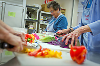 Kathy Perez prepares lettuce for a salad as other volunteers at the St. Thomas Soup Kitchen in Coeur d'Alene prepare other vegetables for the organization's weekly dinner Tuesday.
