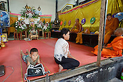 "Mar. 21, 2009 -- BANGKOK, THAILAND: People wait for a funeral to start in a home in the Monk's Bowl Village in Bangkok. The Monk's Bowl Village on Soi Ban Baat in Bangkok is the only surviving one of what were originally three artisan's communities established by Thai King Rama I for the purpose of handcrafting ""baat"" the ceremonial bowls used by monks as they collect their morning alms. Most monks now use cheaper factory made bowls and the old tradition is dying out. Only six or seven families on Soi Ban Baat still make the bowls by hand. Most of the bowls are now sold to tourists who find their way to hidden alleys in old Bangkok. The small family workshops are only a part of the ""Monk's Bowl Village."" It is also a thriving residential community of narrow alleyways and sidewalks.     Photo by Jack Kurtz"