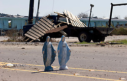 08 Sept 2005. New Orleans, Louisiana.  Hurricane Katrina aftermath. <br /> Venetian Isles in East New Orleans, where the tidal surge washed over the land and devastated homes and property. Two Mother Mary figurines stand in the middle of the Chef Menteur Highway amidst the hurricane damage.<br /> Photo; ©Charlie Varley/varleypix.com