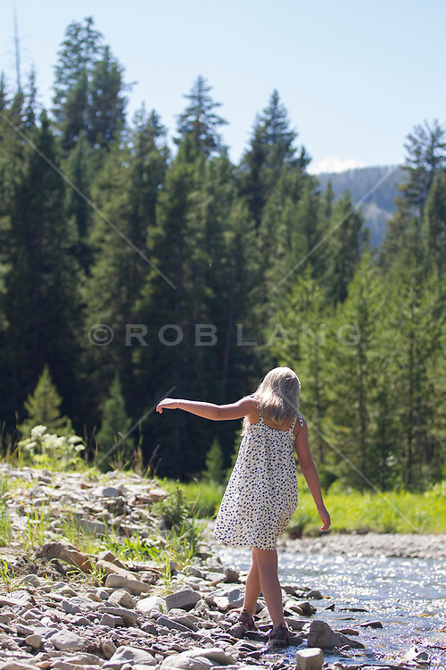 little blonde girl walking by a stream in Montana