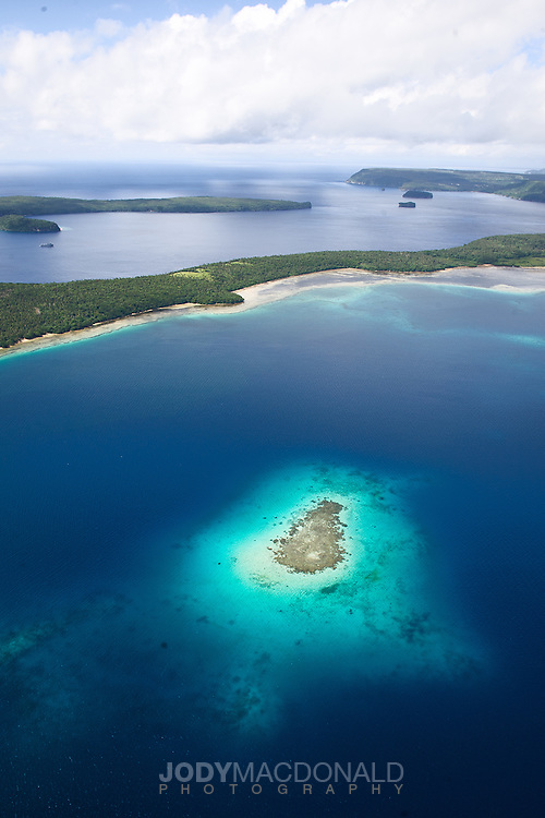 Paragliding over the vavau group in Tonga with reef and this strip of island below