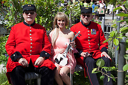 © licensed to London News Pictures. LONDON, UK  23/05/2011. Chelsea Flower Show, Press Day. Electric violinist Alexandra with two Chelsea Pensioners in the Doncaster Deaf Trust Garden.  Please see special instructions for usage rates. Photo credit should read Bettina Strenske/LNP