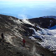 People explore the crater rim as gasses from the volcano emerge from vents during a summit of Mount Rainier on June 30, 2015. The iconic Pacific Northwest volcano is a popular challenge for mountaineers.  (Joshua Trujillo, seattlepi.com)