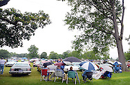 A group of people sit under umbrellas at the car show portion of Quakertown Community Day at Memorial Park Saturday July 4, 2015 in Quakertown, Pennsylvania. (Photo by William Thomas Cain)