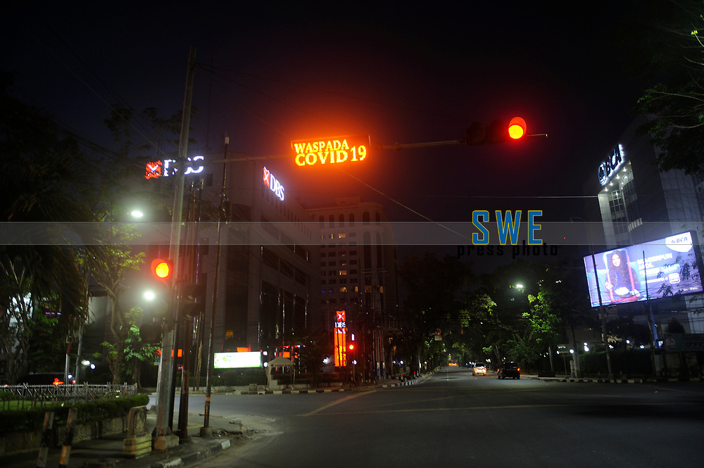 Medan, Indonesia, March 25, 2020: An Indonesian government appeal to be wary of the spread of the Corona Virus Disease (COVID) 19 seen at the traffic lights with the background international hotel and bank were quiet silent on March 25, 2020.