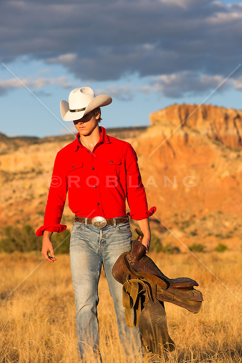 sexy cowboy with a saddle outdoors at sunset in the mountains