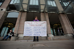 © licensed to London News Pictures. London, UK 23/10/2012. A protester with a banner waiting outside  Portcullis House for BBC director general George Entwistle whilst giving evidence to Commons Culture Committee on BBC's response to Jimmy Savile affair . Photo credit: Tolga Akmen/LNP