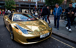 Passers-by admire a gold Ferrari 458 Spider owned by kickboxing world champion Riyadh Al-Azzawi as it is parked outside Harrods department store in Knightsbridge, London.
