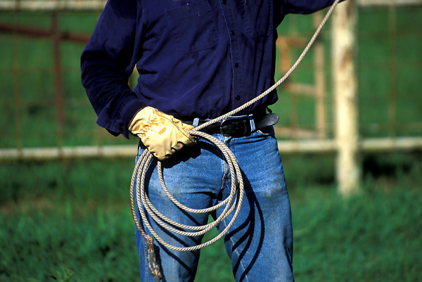 close up of a cowboy holding and  swinging a lasso
