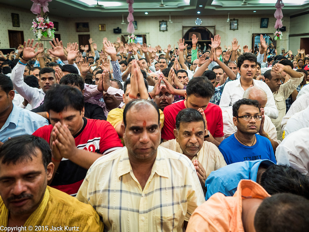 05 SEPTEMBER 2015 - BANGKOK, THAILAND:  Men pray at midnight, the time of Krishna's birth, during Janmashtami services in the Vishnu Temple in Bangkok. Janmashtami is the annual celebration of the birth of the Hindu deity Krishna, the eighth avatar of Vishnu. Hindus celebrate Janmashtami by fasting, worshipping Krishna and staying up until midnight, the time when Krishna is believed to have been born. At midnight they pray and exchange small gifts.    PHOTO BY JACK KURTZ