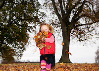 Girl (3-4) playing in autumn leaves