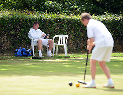 © Licensed to London News Pictures. 14/08/2013. Surbiton, UK. Ian Lines, England plays while his opponent David Maugham, England relaxes. People participate in the14th World Association Croquet Championship at the Surbiton Croquet Club, Kingston upon Thames on the 14th August 2013. The Final will be played on Sunday 18th August. 80 competitors from 20 countries are taking part. Photo credit : Mike King/LNP