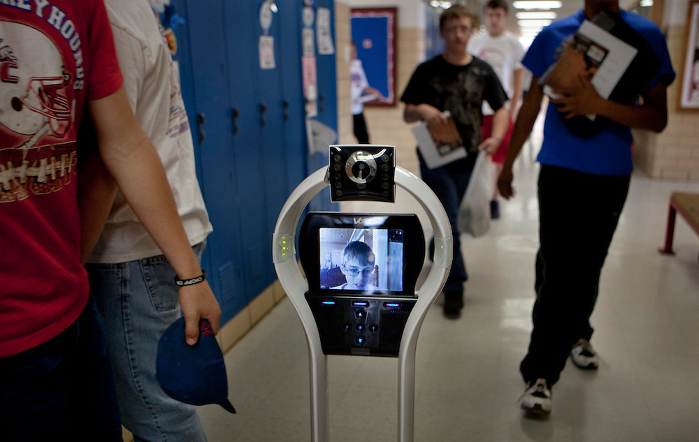 Lyndon Baty, 15, operating his robot from his home computer, he drives his robot along the corridors of his school on his way to class. He goes to school and church via a robot that has a camera and videoconferencing capacity. Born with kidney disease, his body is now rejecting the kidney he had transplanted when he was 7. With little or no immune system, it is too risky for him to be near people other than his direct family members. He lives in Knox City, Texas, with his parents and two brothers.