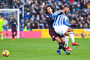 Elias Kachunga of Huddersfield Town (9) is fouled by Matteo Guendouzi of Arsenal (29) during the Premier League match between Huddersfield Town and Arsenal at the John Smiths Stadium, Huddersfield, England on 9 February 2019.