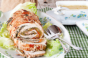 Turkey roll served with vegetables sauce.