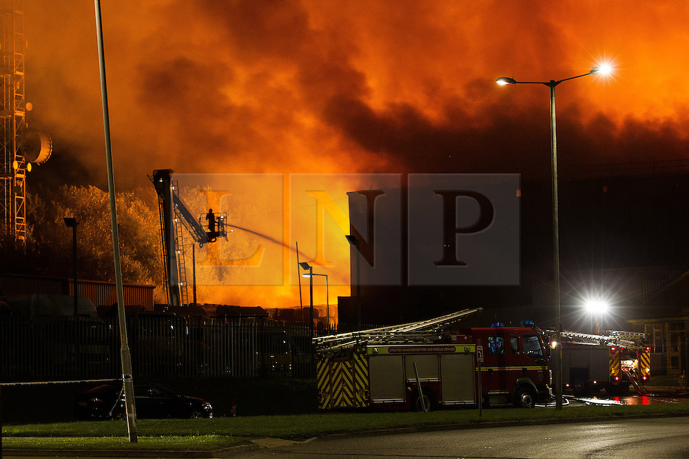 © Licensed to London News Pictures . 21/08/2013 . Stockport , UK . Firefighters use elevated platforms to tackle a large blaze at the J25 Recycling Centre in Bredbury , Stockport this morning (Wednesday 21st August 2013) where a building and bales of recyclable material are alight . The fire , which started late last night (20th August) is being tackled by more than 50 fire crew . The site , which is adjacent to a branch of Morrisons Supermarket and McDonalds , is off Junction 25 of the M60 motorway , exits for which are closed in both directions . Photo credit : Joel Goodman/LNP