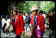 Two old men in red jackets carry purple flags as they lead tour group at Toshogu Shrine; Nikko. Japan