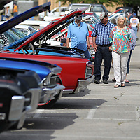 Charles Jackson, left, of Graham Alabama, Jerry Wiggins and his wife, Emma, of Bowden Georgia make thier way down the first row of cars Friday morning at the annual Blue Suede Cruise in Tupelo.