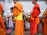 "11 MARCH 2013 - LUANG PRABANG, LAOS: Buddhist monks collect food during the tak bat. The ""Tak Bat"" is a daily ritual in most of Laos (and other Theravada Buddhist countries like Thailand and Cambodia). Monks leave their temples at dawn and walk silently through the streets and people put rice and other foodstuffs into their alms bowls. Luang Prabang, in northern Laos, is particularly well known for the morning ""tak bat"" because of the large number temples and monks in the city. Most mornings hundreds of monks go out to collect alms from people.    PHOTO BY JACK KURTZ"