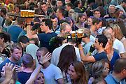 Nederland, Nijmegen, 16-7-2014 Recreatie, ontspanning, cultuur, dans, theater en muziek in de binnenstad tijdens de zomerfeesten. Hier op het volle Koningsplein. Een van de tientallen feestlocaties in de stad. Onlosmakelijk met de vierdaagse, 4daagse, zijn in Nijmegen de vierdaagse feesten, de zomerfeesten. talrijke podia staat een keur aan artiesten, voor elk wat wils. Een week lang elke avond komen tegen de honderdduizend bezoekers naar de stad. De politie heeft inmiddels grote ervaring met het spreiden van de mensen, het zgn. crowd control.De vierdaagsefeesten zijn het grootste evenement van Nederland en verbonden met de wandelvierdaagse. Bier,drinken,alkohol,alcohol,drank,blad, dienblad met volle glazen. Foto: Flip Franssen/Hollandse Hoogte